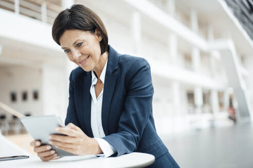 Smiling businesswoman using digital tablet while working in office - JOSEF03649