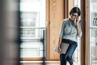 Female entrepreneur talking on smart phone while leaning over window at office - JOSEF03655