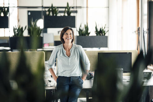 Smiling businesswoman with hands in pockets leaning on desk at office - JOSEF03664