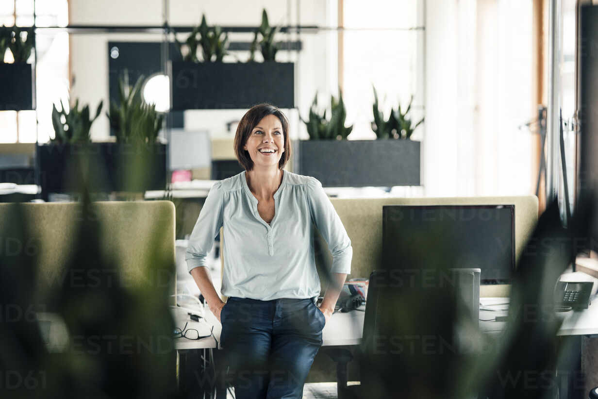 Smiling businesswoman with hands in pockets leaning on desk at office - JOSEF03664 - Joseffson/Westend61