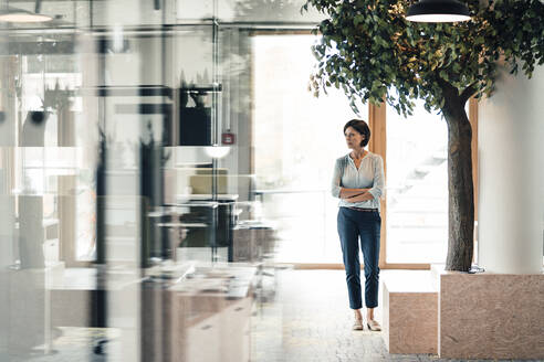 Confident businesswoman with arms crossed standing in office - JOSEF03667