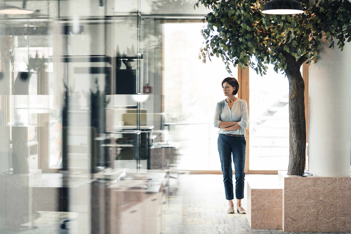 Confident businesswoman with arms crossed standing in office - JOSEF03667 - Joseffson/Westend61