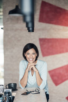 Happy businesswoman with hand on chin at table in office - JOSEF03673