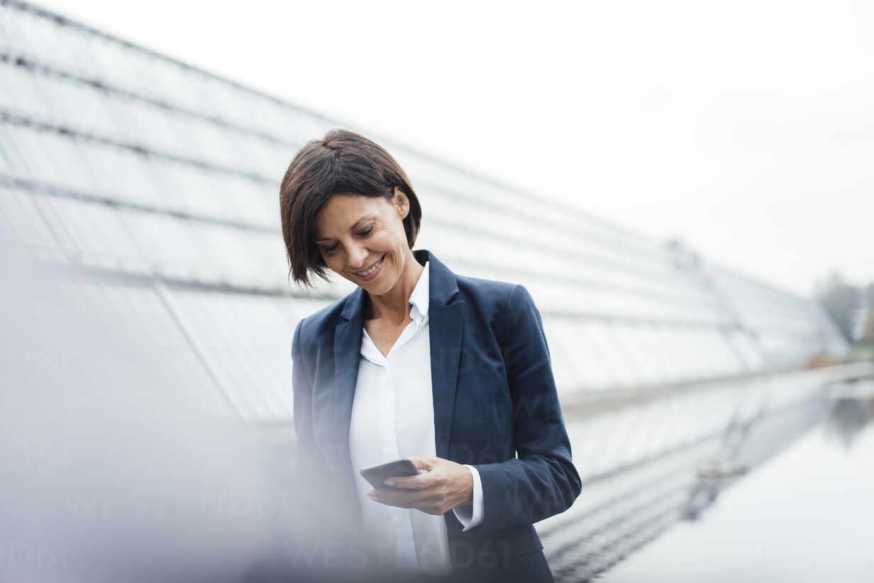 Smiling businesswoman text messaging on smart phone outside office building - JOSEF03685 - Joseffson/Westend61