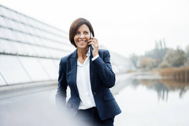 Smiling businesswoman talking on smart phone outside office - JOSEF03688