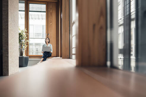 Female entrepreneur with laptop sitting on alcove widow seat at office - JOSEF03709