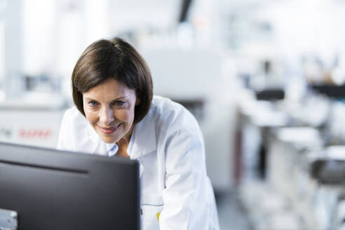 Smiling female engineer using computer at factory - JOSEF03718