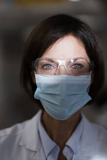 Female scientist with protective eyewear at laboratory during pandemic - JOSEF03724