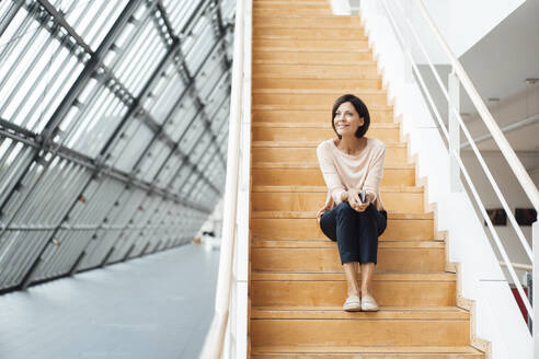 Female businesswoman contemplating while sitting on steps at corridor - JOSEF03730