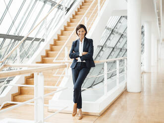 Smiling confident businesswoman with arms crossed by railing in corridor - JOSEF03739