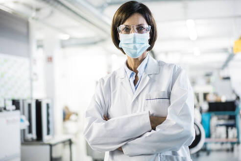 Female scientist with arms crossed at laboratory during pandemic - JOSEF03754