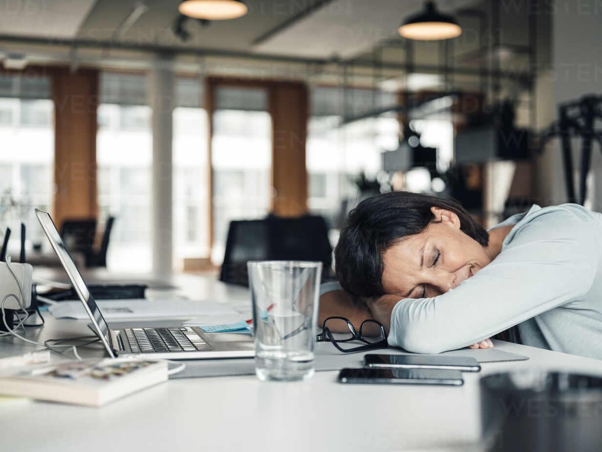 Businesswoman with head down relaxing on desk at office - JOSEF03760 - Joseffson/Westend61