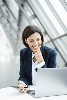 Smiling businesswoman with hand on chin working on laptop in corridor - JOSEF03772