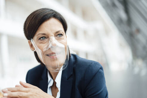 Female professional with protective face mask at office - JOSEF03775