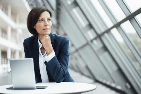 Female professional contemplating by digital tablet in corridor - JOSEF03778