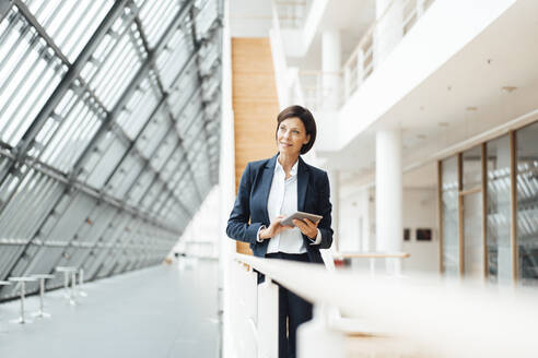 Businesswoman with digital tablet contemplating at corridor - JOSEF03784
