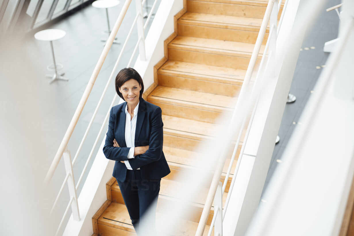 Selbstbewusste Geschäftsfrau mit verschränkten Armen steht auf Stufen im Korridor - JOSEF03787 - Joseffson/Westend61