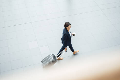 Businesswoman with suitcase walking in corridor - JOSEF03793