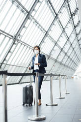 Businesswoman with suitcase standing in corridor during pandemic - JOSEF03796