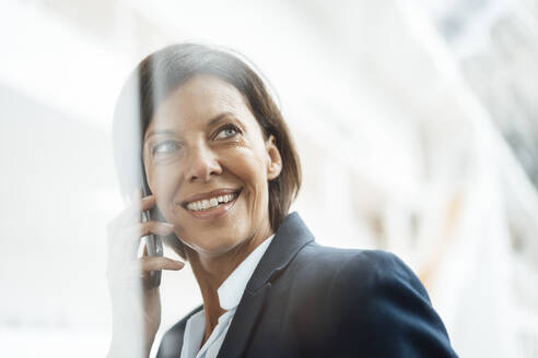 Smiling businesswoman talking on mobile phone at office - JOSEF03805