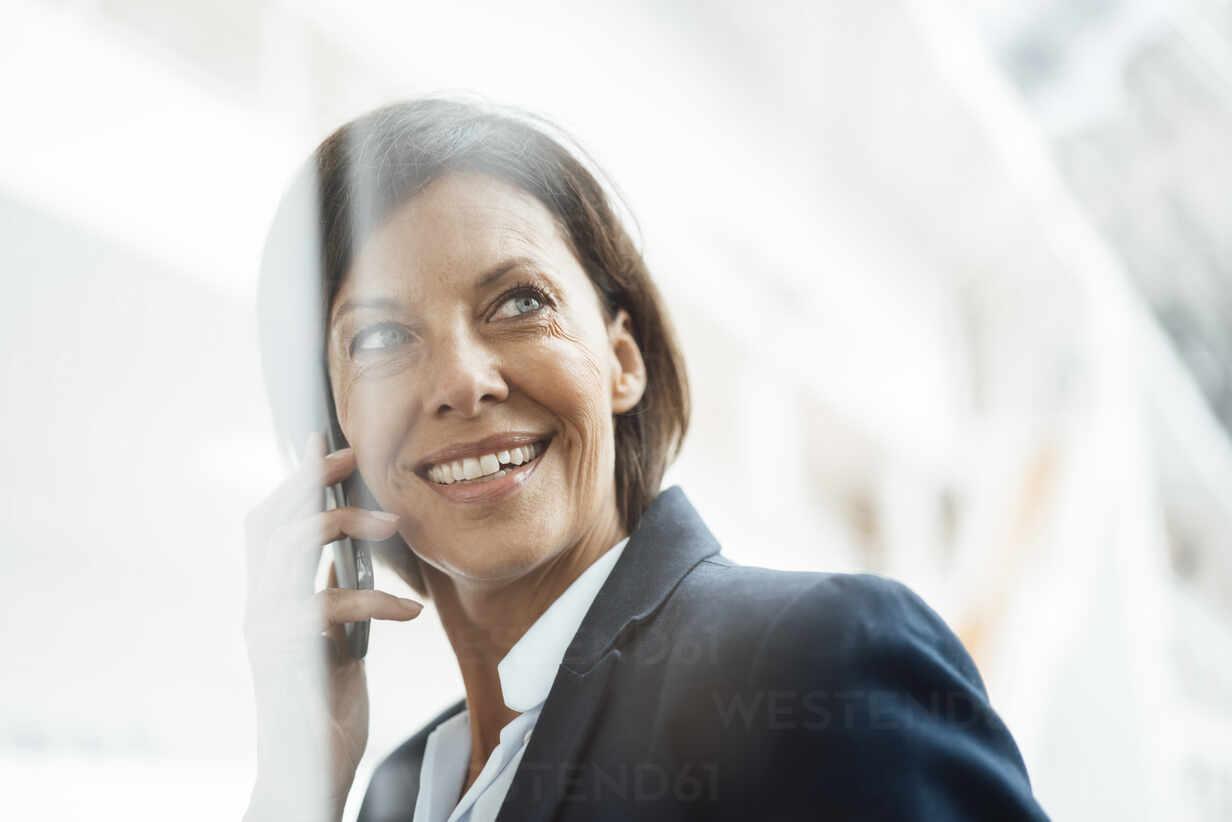 Lächelnde Geschäftsfrau spricht am Handy im Büro - JOSEF03805 - Joseffson/Westend61