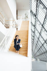 Businesswoman with digital tablet and hand on chin sitting over steps in corridor - JOSEF03808
