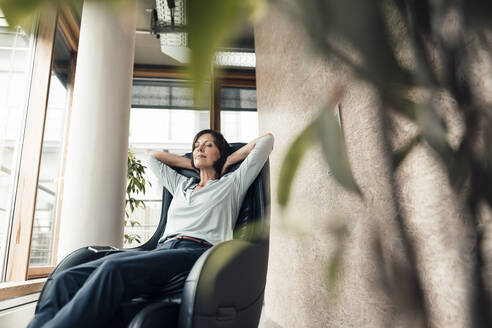 Businesswoman with hands behind head sitting on armchair in office - JOSEF03814