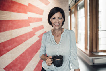 Confident female entrepreneur with coffee cup in office - JOSEF03817