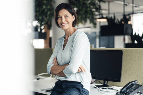 Smiling female entrepreneur with arms crossed against computer in office - JOSEF03820
