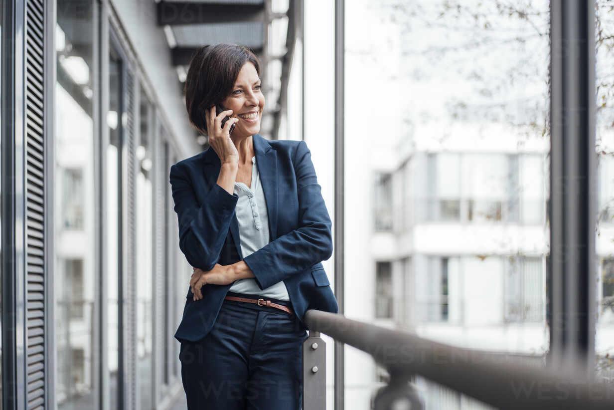 Glückliche Geschäftsfrau spricht auf Handy im Büro Balkon - JOSEF03832 - Joseffson/Westend61