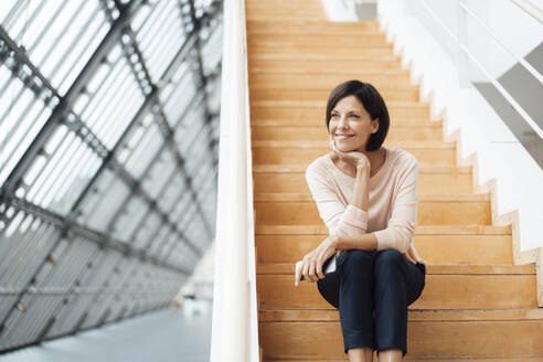 Smiling businesswoman with hand on chin sitting on steps at corridor - JOSEF03838