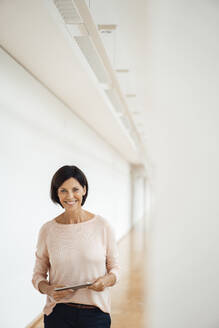 Smiling businesswoman holding digital tablet standing in corridor at office - JOSEF03847