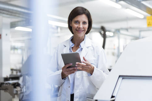 Smiling female scientist with digital tablet at laboratory - JOSEF03862