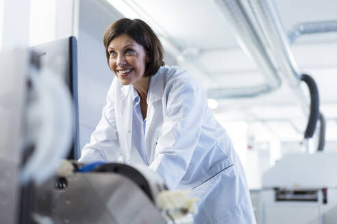 Smiling female scientist examining machinery at laboratory - JOSEF03865