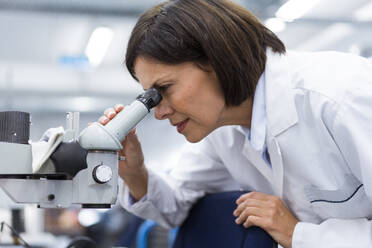 Female scientist using microscope while working in laboratory - JOSEF03871