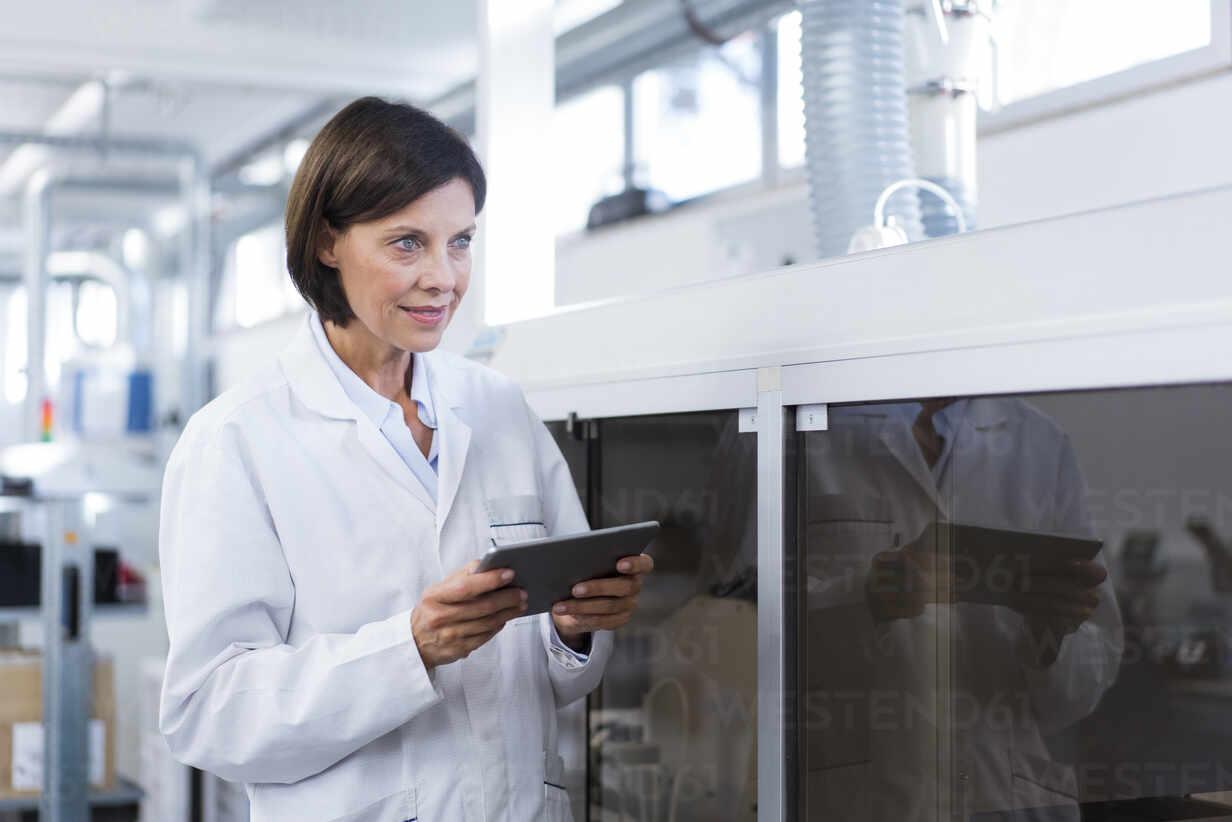 Weiblicher Techniker mit digitalem Tablet, der in der Fabrik wegschaut - JOSEF03874 - Joseffson/Westend61