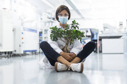 Mature female scientist with potted plant sitting in laboratory during COVID-19 - JOSEF03886