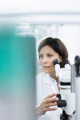Mature female scientist with microscope at laboratory - JOSEF03895