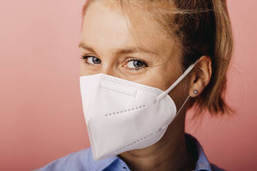Businesswoman wearing protective face mask staring while standing against colored background - DAWF01785