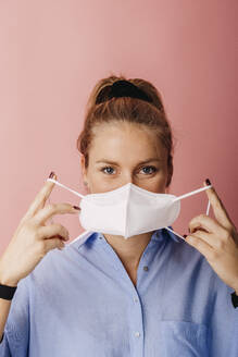 Mid adult businesswoman wearing protective face mask while standing against colored background - DAWF01788