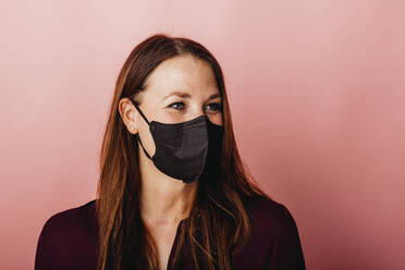 Young female entrepreneur wearing protective face mask looking away while standing against colored background - DAWF01791