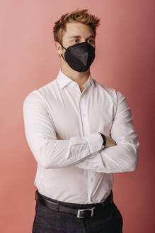Male entrepreneur wearing FFP2 face mask looking away while standing with arms crossed against colored background - DAWF01794