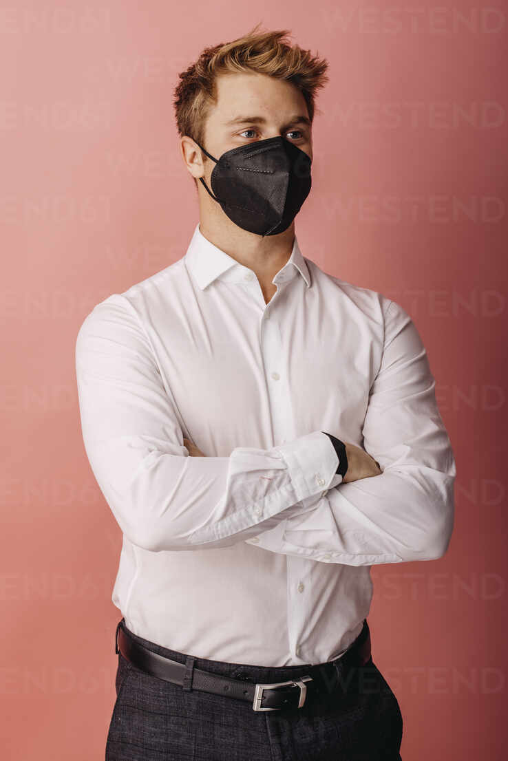 Male entrepreneur wearing FFP2 face mask looking away while standing with arms crossed against colored background - DAWF01794 - Daniel Waschnig Photography/Westend61
