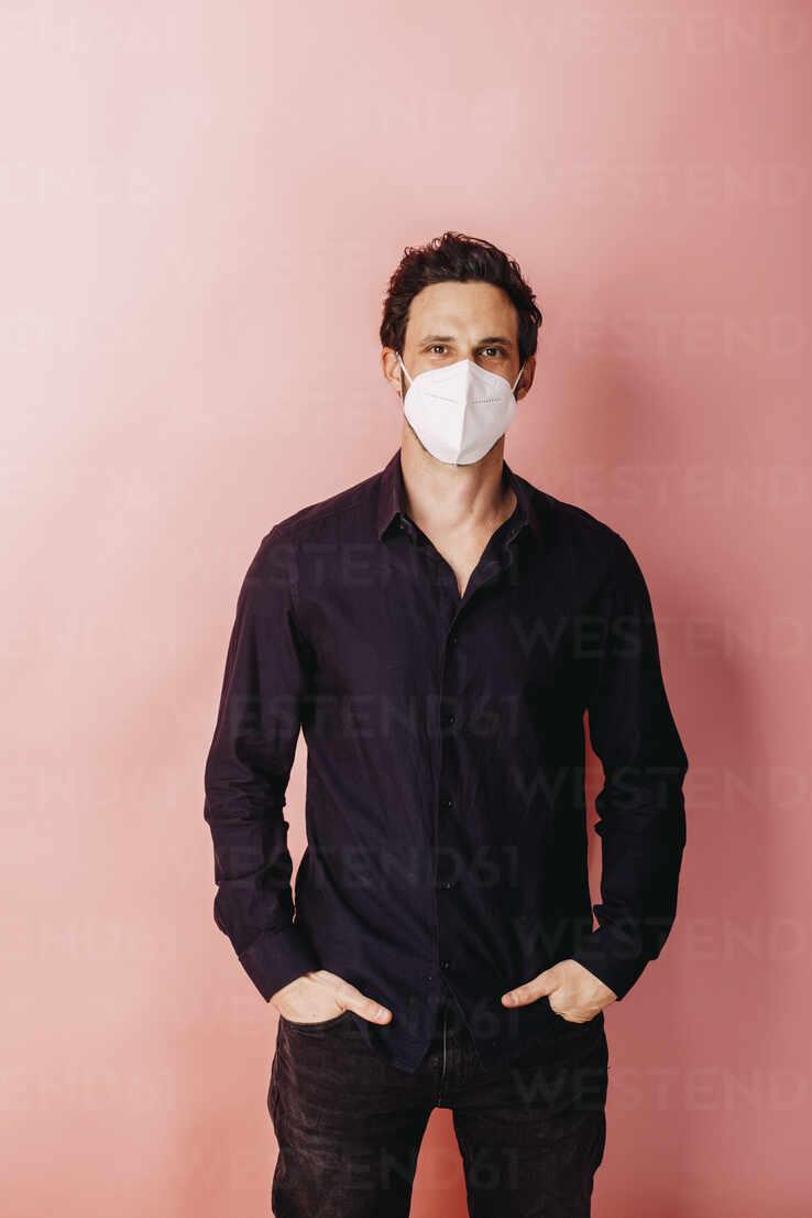 Geschäftsmann mit Schutzgesichtsmaske stehend mit Händen in den Taschen gegen farbigen Hintergrund - DAWF01797 - Daniel Waschnig Photography/Westend61