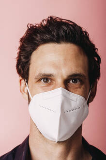 Businessman wearing protective face mask staring while standing against colored background - DAWF01800