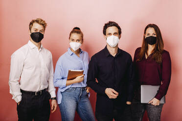 Business people wearing protective face mask staring while standing against colored background - DAWF01803