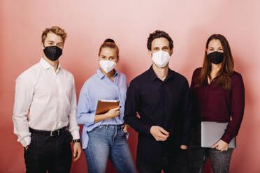 Gruppe mit FFP2 Maske vor Rosa Beige Hintergrund. Österreich, Kärnten, Klagenfurt - DAWF01803
