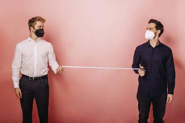 Zwei Personen mit Maske zeigen Mindesabstand vor farbigen Hintergrund. Österreich, Kärnten, Klagenfurt - DAWF01809
