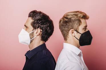 Zwei Personen mit Maske vor farbigen Hintergrund. Österreich, Kärnten, Klagenfurt - DAWF01812