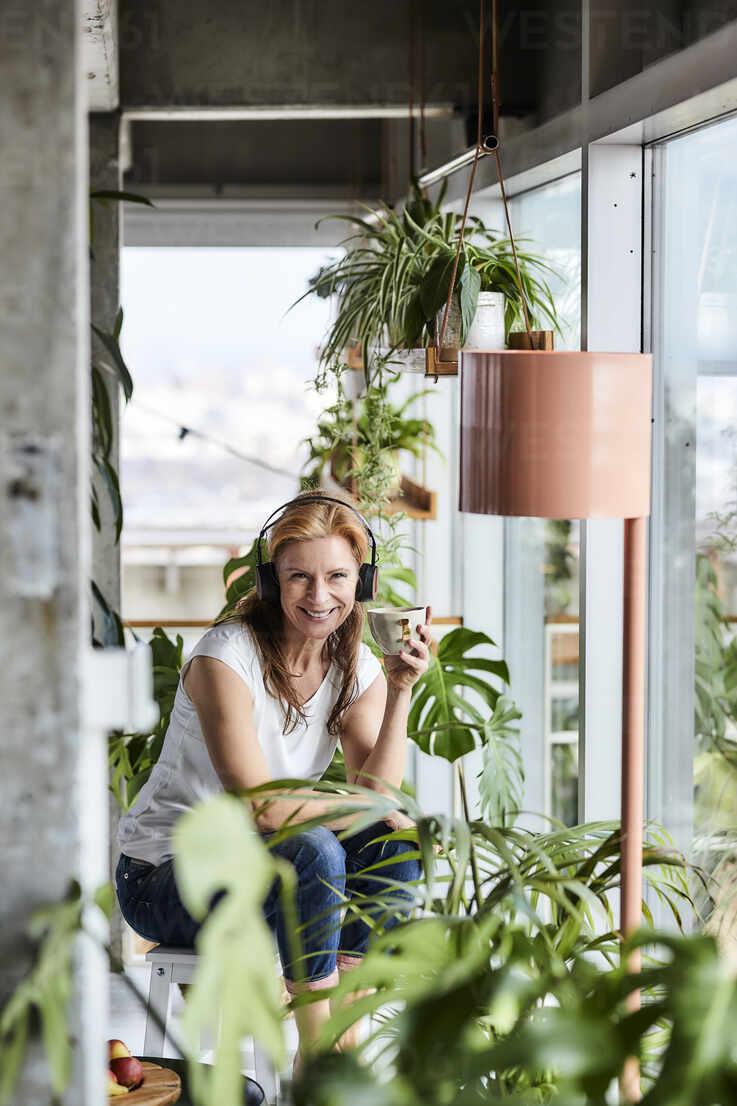 Lächelnde reife Frau mit Kopfhörern Musik hören, während mit Kaffee in Balkon - FMKF06974 - Jo Kirchherr/Westend61